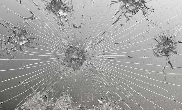 Textuur van gebarsten glas op grijze achtergrond.