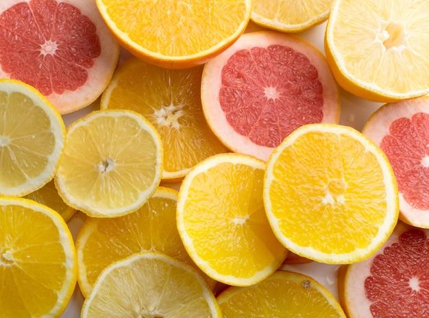 Textuur van gesneden citroen, sinaasappel en rode grapefruit plat lag en bovenaanzicht. oppervlak met veelkleurige vruchten