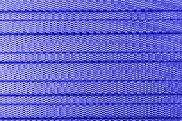 Textuur van gestreepte kunststof metalen hitech ruw lichtgewicht materiaal. klassieke blauwe kleurenachtergrond