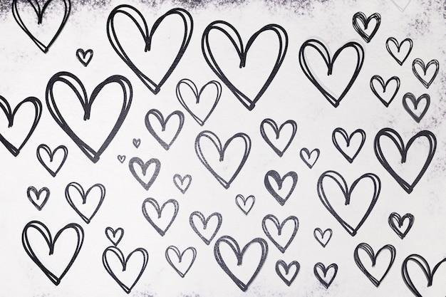 Textuur van getrokken harten in zwart op een witte achtergrond van bloem. valentijnsdag.