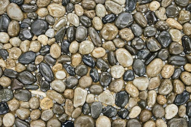 Textuur van gladde stenen die decoratief op de grond zijn aangelegd landschapsontwerpfragment