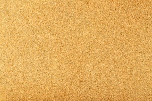 Textuur van goudkleurig zand op het strand met een stevig oppervlak op volledig scherm