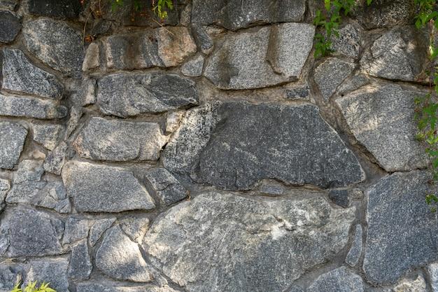 Textuur van granietmetselwerkmuur in zonlicht voor patroon, muur of 3d. horizontaal, close-up. ruw oppervlak van constructie