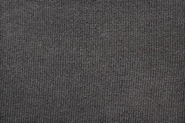 Textuur van grijze gebreide stof, close-up
