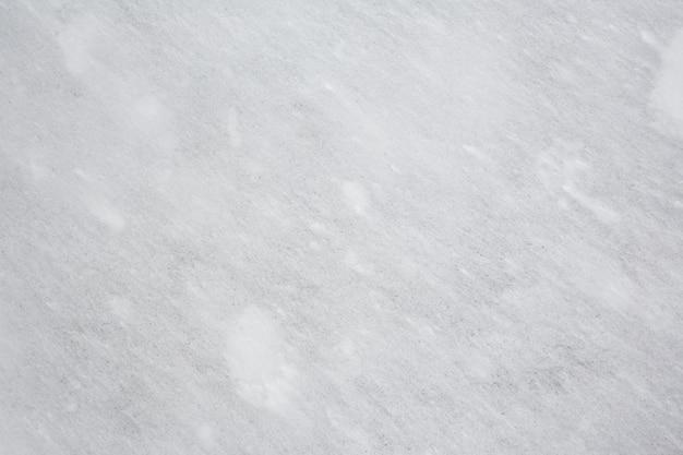 Textuur van grijze steen bedekt met dunne laag witte sneeuw