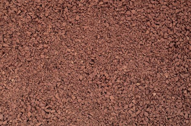 Textuur van grondkoffie in de vorm van vele kleine kiezelstenen van donkere bruine kleur
