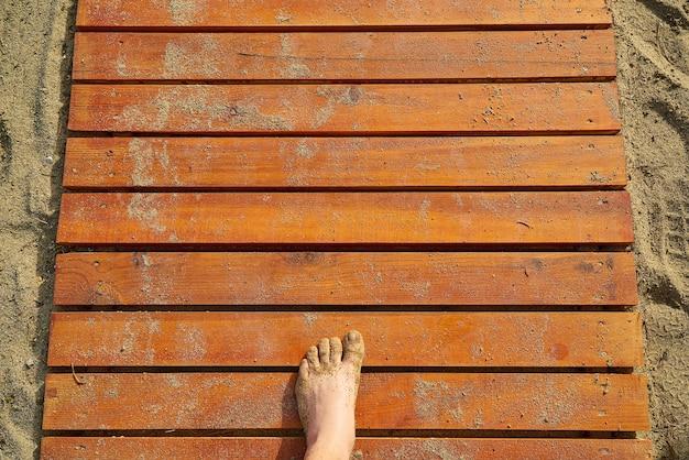 Textuur van houten planken met zand en een voet