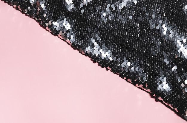 Textuur van kostbare zwarte en zilveren pailletten die ronde lovertjes op roze achtergrond schijnen.