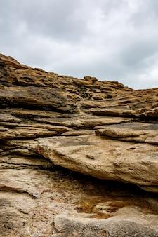 Textuur van kust oude steen. rots behang. bewolkte lucht