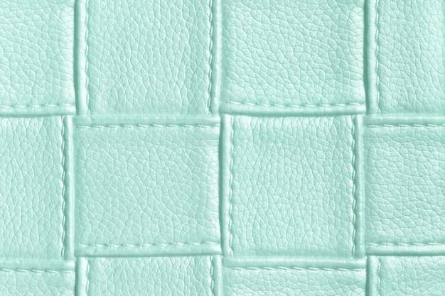 Textuur van lichtblauw en cyaan leerachtergrond met vierkant patroon en steek, macro.