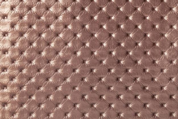Textuur van lichtbruine leerachtergrond met capitonepatroon, macro. bronzen textiel in retro chesterfield-stijl. vintage stof.