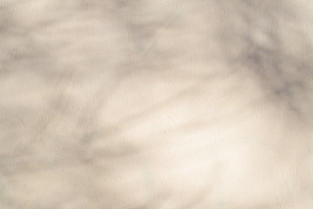 Textuur van lichtgele muur met schaduw van boom op zonnige dag. kopieer ruimte achtergrond