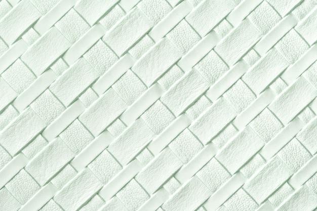 Textuur van lichtgroene leerachtergrond met rieten patroon, macro.