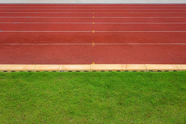Textuur van lopende renbaan rode rubberrenbanen in openluchtstadion