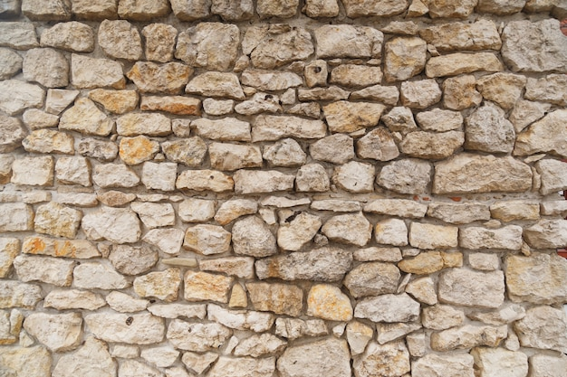 Textuur van middeleeuwse oude licht gekleurde stenen muur.