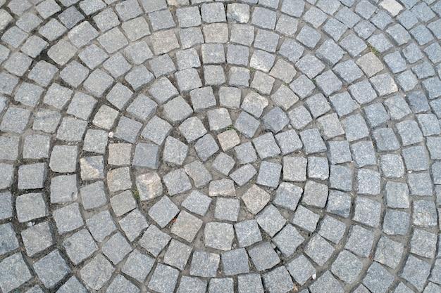 Textuur van oud cobbled-bestratingsclose-up. abstracte granieten stenen achtergrond.