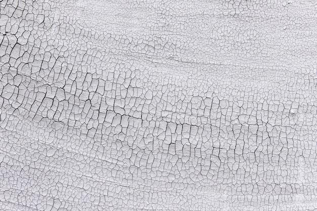 Textuur van oud doorstaan pleister met barsten