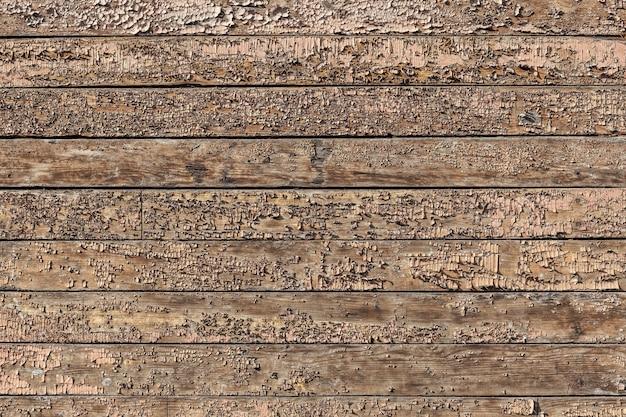 Textuur van oude bruine houten muur met gebarsten verf.