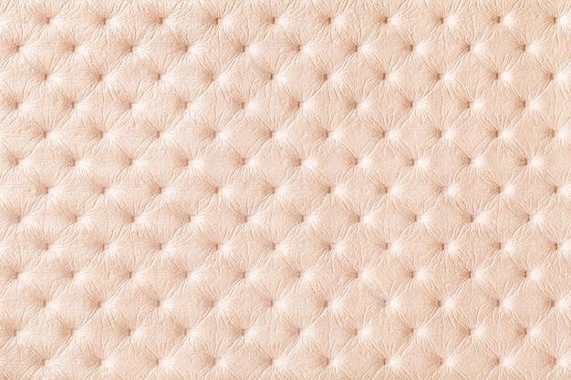 Textuur van parel beige leer stof achtergrond met capitonner stijl. crème textiel in chesterfield-stijl.