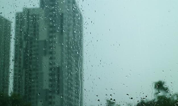 Textuur van regendruppels op vensterglas met wazige wolkenkrabbers en bewolkte lucht op de achtergrond