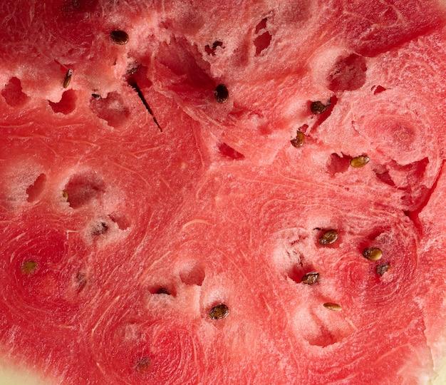 Textuur van rijpe rode watermeloen met bruine zaden, volledig frame, close-up