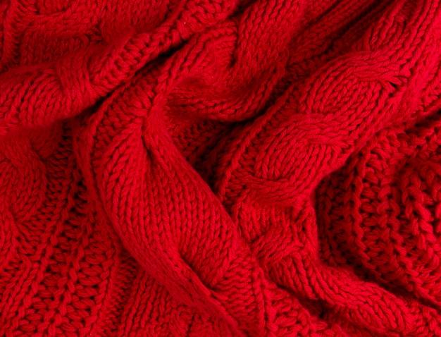Textuur van rode gebreide stof dicht omhoog. wollen gebreide kleding