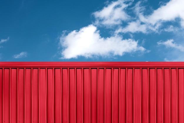 Textuur van rode vrachtschipcontainer die met blauwe hemelachtergrond wordt gevestigd