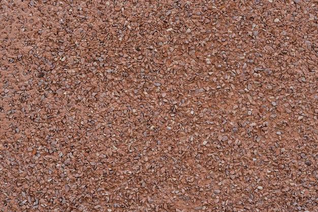 Textuur van rood uiterst klein grind dat met cement wordt gemengd