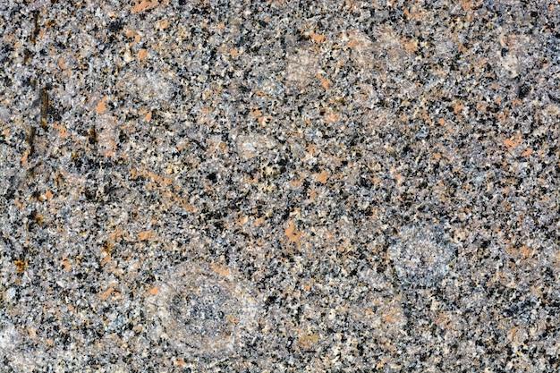 Textuur van stenen op wegclose-up. deel van een weg geplaveid met vierkante stenen van rood graniet.