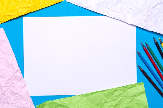 Textuur van verfrommeld gekleurd papier, potloden en canvas voor tekening.