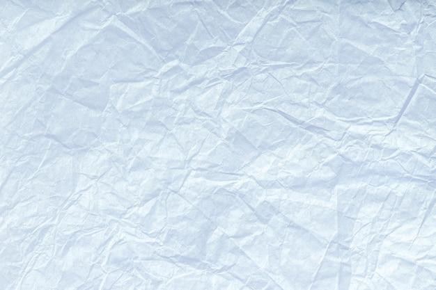 Textuur van verfrommeld lichtblauw verpakkend document, close-up. witte oude achtergrond.
