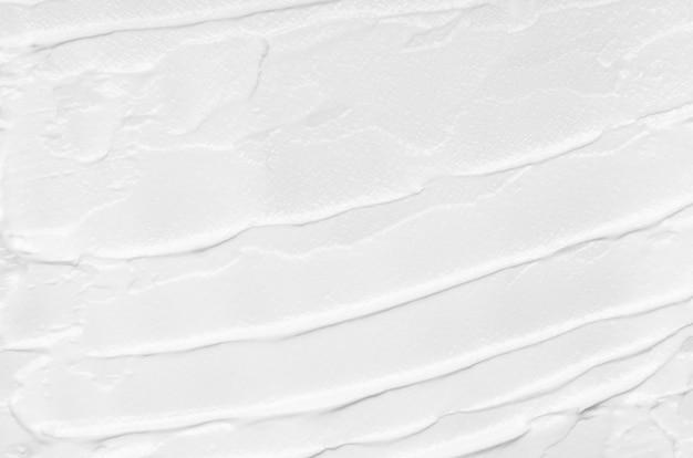 Textuur van witte gezichtscrème die op een witte achtergrond wordt gesmeerd