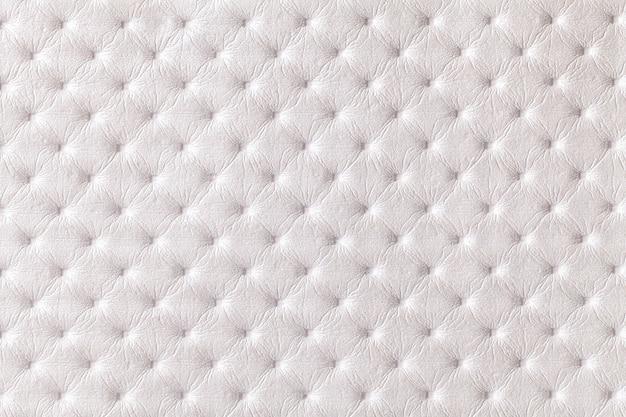 Textuur van witte leerachtergrond met capitone patroon, macro. parelmoer textiel in retro chesterfield stijl. vintage stof.
