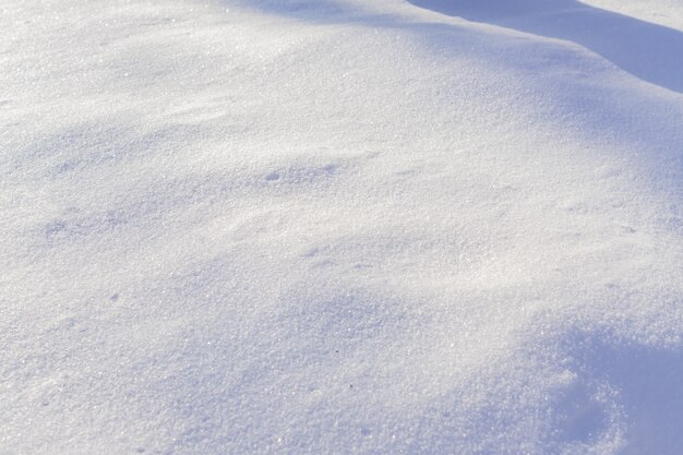 Textuur van witte sneeuw die op de zon fonkelt.