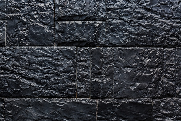 Textuur van zwarte steenmuur voor achtergrond