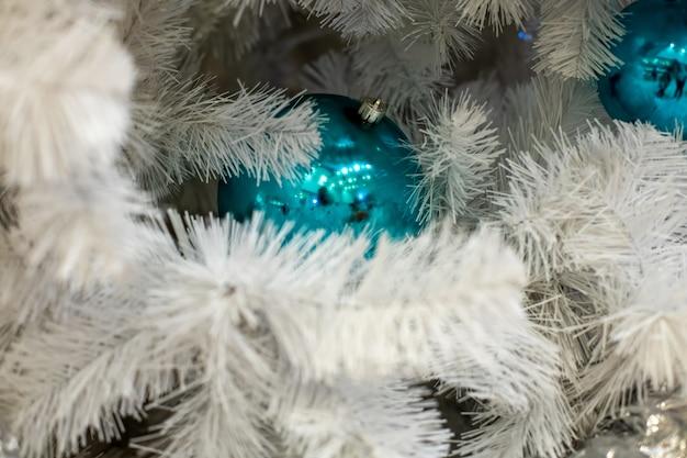 Textuur witte spartak met klassiek blauw balspeelgoed. een fragment van het nieuwe jaar en de kerstboom. close-up, zachte focus, achtergrond wazig