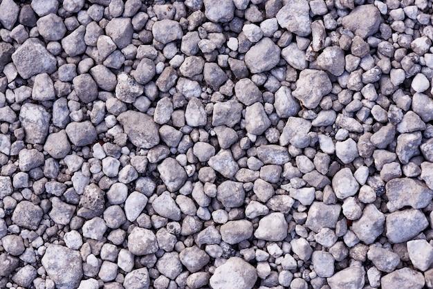 Textuurachtergrond van vele kleine grijze stenen.