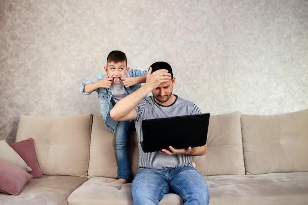 Tfather met laptop aan het werk terwijl het kind speelt