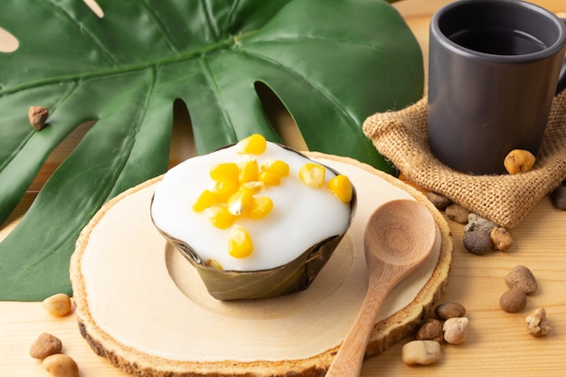 Thai pudding kokosnoot top met maïs, desserts verpakt in bananenbladeren.thaise mensen noemen