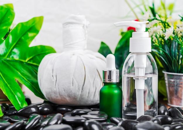 Thai spa-massage-instelling met serumolieflesdruppelaarmodel of etherische olie en thaise kruidenkompresballen op zwarte steen tegen groene verlofachtergrond