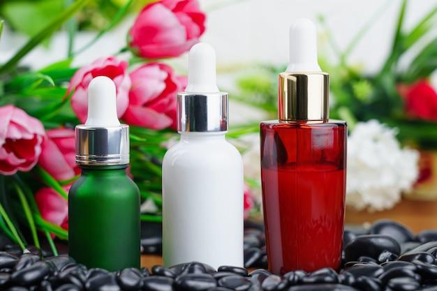 Thai spa massage setting met serum oliefles druppelaar mock up of etherische olie op zwarte steen tegen bloemachtergrond