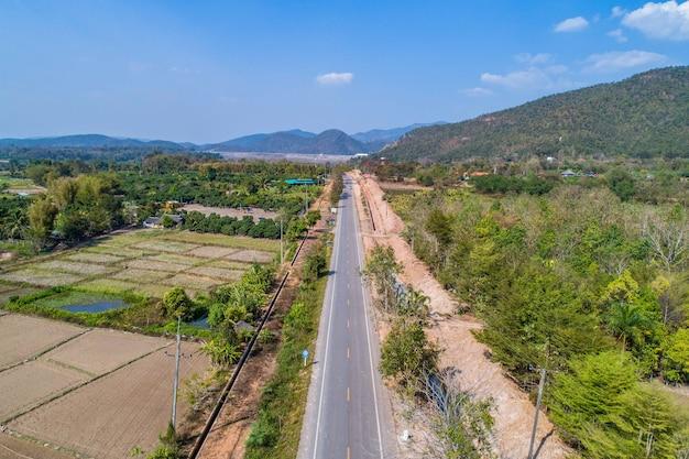 Thailand landelijke weg (schieten vanuit drone) die de weg naar de berg gaat met het veld en de vallei ernaast, ten noorden van thailand.