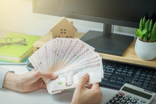 Thailand notebank geld houden door vrouw hand op bureau