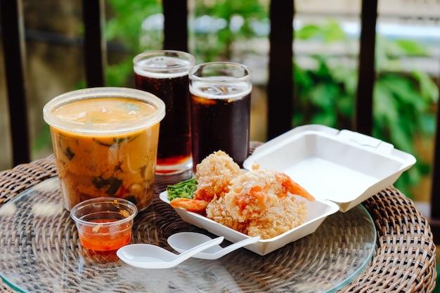 Thais afhaalmaaltijden. tom kha-soep en gebakken garnalen in beslag