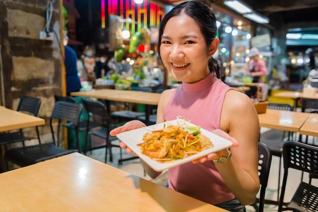 Thais-chinese toeristen slenteren rond en proeven straatvoedsel op yaowarat road, chinatown, bangkok