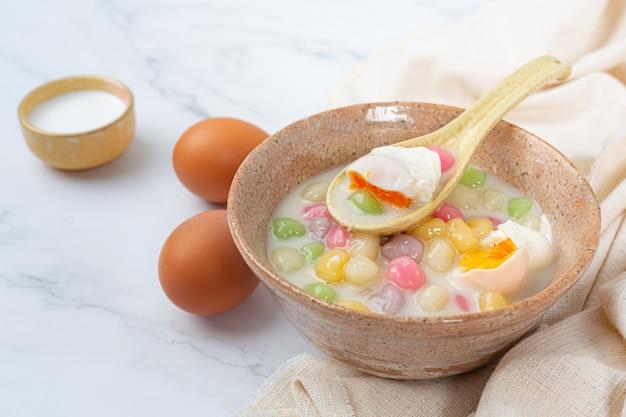 Thais dessert genaamd bualoy-ballen in dippers met hete kokosmelk en pandanbladeren om de verrukking te vergroten.