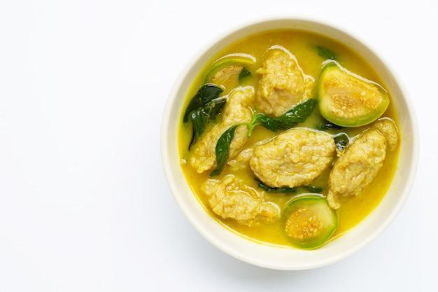 Thais eten. groene curry met visbal op wit