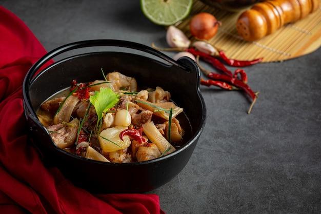 Thais eten met de pittige soep van het varkensvleesbeen in zwarte kom