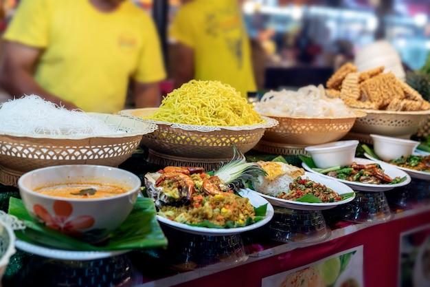 Thais eten op de markt in phuket noedels tom yam soepsalades en traditioneel straatvoedsel van thailan...