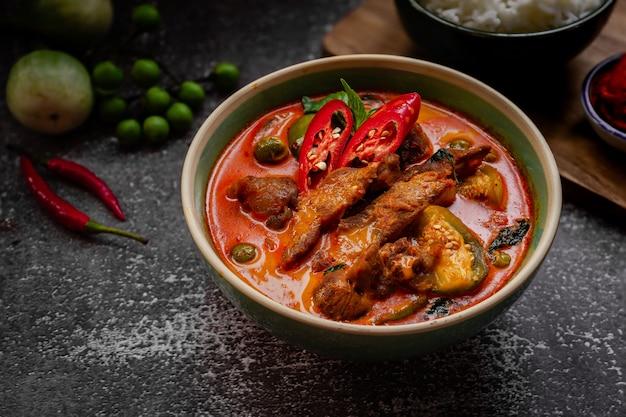 Thais eten - pittige varkensvlees rode curry met ingrediënten op donkere tafel